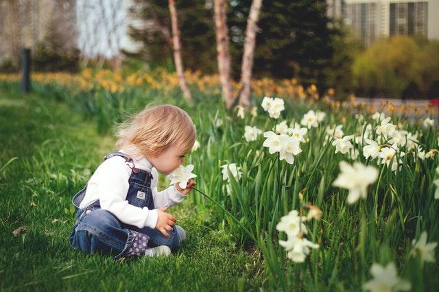 girl sitting on grass smelling white flower