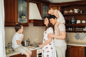 family preparing crepes together in green kitchen