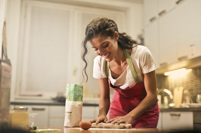 happy woman with rolling pin cooking in her green kitchen